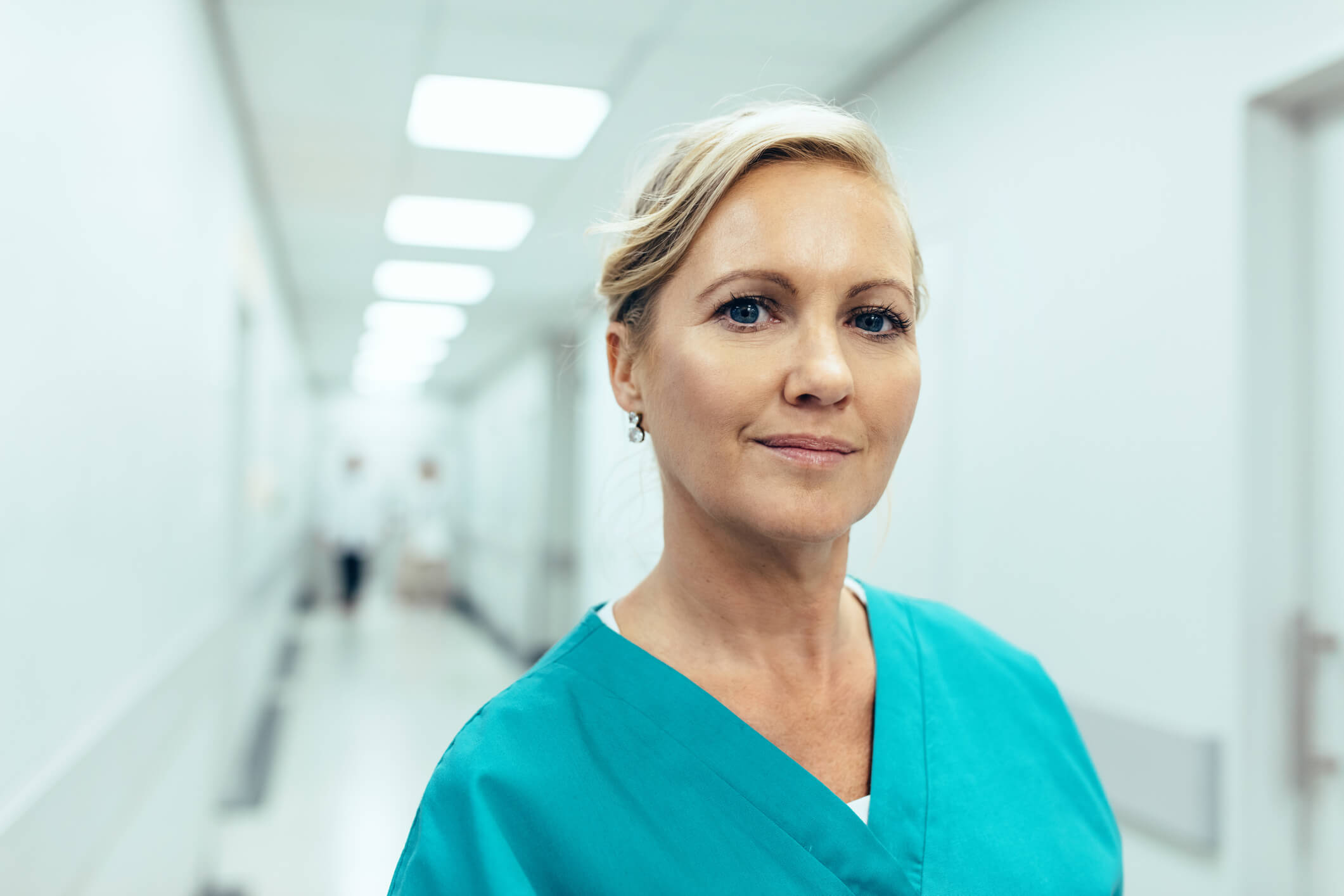 Close up portrait of female healthcare worker standing in hospital corridor. Caucasian woman in hospital hallway staring at camera.